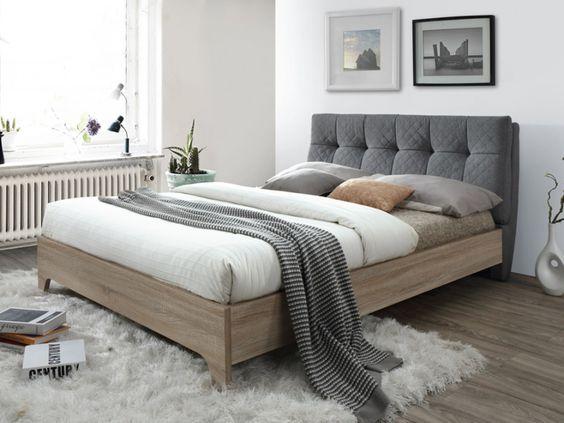 Rénovation de la chambre avec une tête de lit grise, un lit en bois et un gros tapis en laine